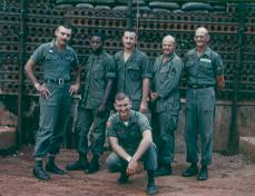"MACV Advisory Team 4 Huong Hoa District Team pictured L-R: MAJ Whitenack, SFC King, LT Clarke, SFC ""Doc"" Perry, SFC Humphries, and SP4 Gehrke (kneeling)."